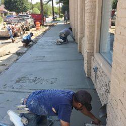 Workers Repair Commercial Sidewalk with Concrete Trowel