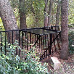 Iron bird feeder attached to iron fence
